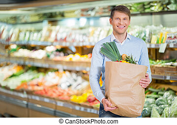 Consumerism - Young man with bag in store