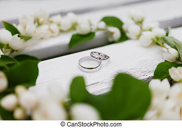 Golden wedding rings with diamonds lie inside jasmine...