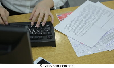 The left hand of a woman typing on a computer keyboard. The...