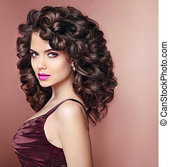 Curly hairstyle. Beautiful smiling woman with makeup and healthy wavy hair style. Beauty fashion portrait. Elegant lady studio portrait.
