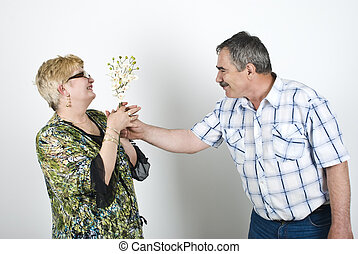 Middle aged man giving flowers to his wife and the woman...