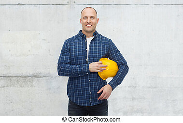 smiling man with helmet over concrete wall - repair,...