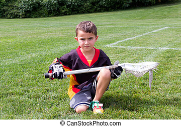 Little boy lacrosse player in the park kneeling down and...