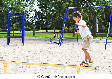 Child playing on the park play structure balance beam -...