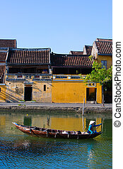 Hoi An scene - Local Vietnamese woman paddling her boat on...