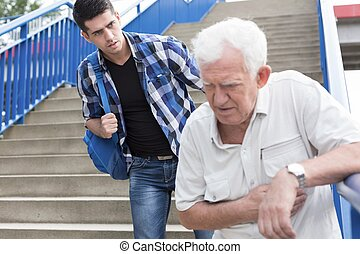 Man giving aid to senior walking downstairs