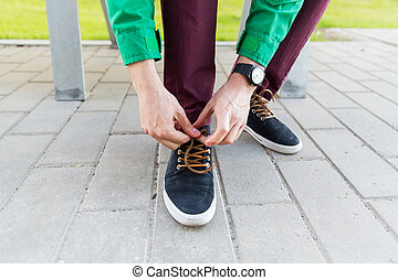 close up of male hands tying shoe laces on street - people,...