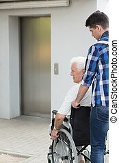 Man on wheelchair - Senior man on wheelchair and helpful boy