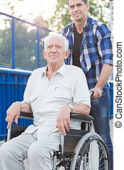 Smiling man on wheelchair - Smiling young man helping...