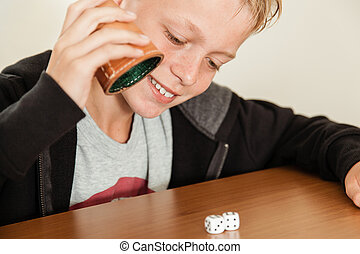 Happy child rolling dice on table - Single happy blond child...