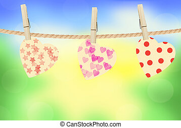 Bright hearts hanging on rope on bright nature background
