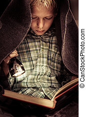 Child reading book under covers with flashlight - Cute...