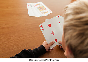 Over the shoulder view of child playing cards - Over the...