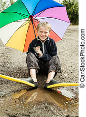 Single child in diving flippers and umbrella - Single happy...