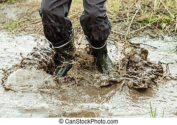 Unidentifiable person jumping in muddy water - Close up on...