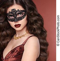 Beauty girl portrait in venetian lace mask. Wavy hairstyle....