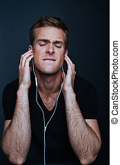 Man is listening to music on white earphones in black v-neck...