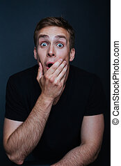 Portrait photo of young man with a surprised expression in v...