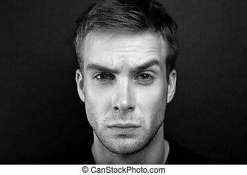 Black and white portrait photo of young man with angry look...