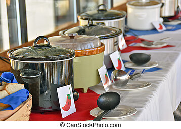 crock pots in chili cook off - Row of crock pots in chili...