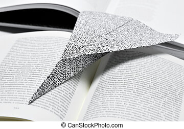 paper plane on an open book - closeup of a paper plane, made...