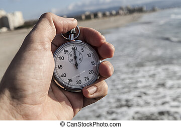 Chronometer In Hand - analog Stopwatch in hand with sea in...
