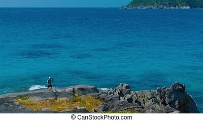 Amateur Photographer Climbing over Beach Rocks in a Tropical...