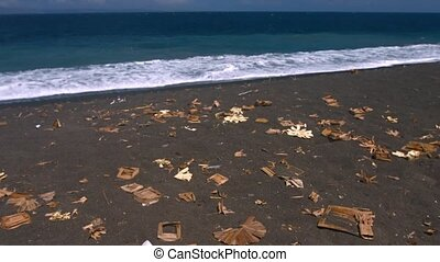 Litter on a Tropical Black Sand Beach in Bali, Indonesia -...