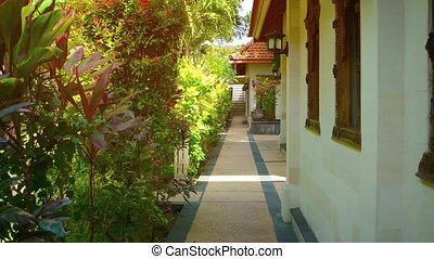 Walkway in the Garden Courtyard of a Luxury Resort Hotel -...