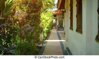 Walkway in the Garden Courtyard of a Luxury Resort Hotel -...