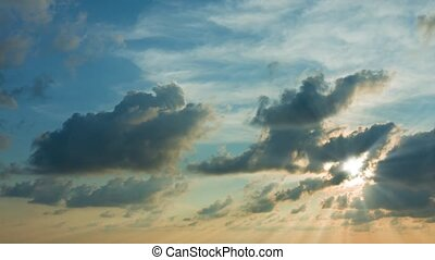 Sunshine Filtering through Puffy Clouds at Sunset - Beams of...