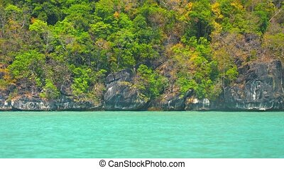 Cruising Past Undercut Limestone Cliffs of a Tropical Island...