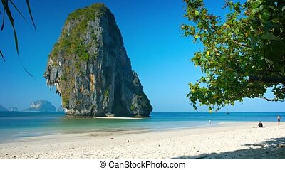 Massive Limestone Formation Towers over Tropical Beach...