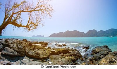 Gentle Waves on a Rocky Tropical Beach on a Sunny Day -...