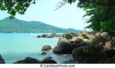 quot;Water Splashes on Shaded, Rocky, Tropical Beachquot; -...