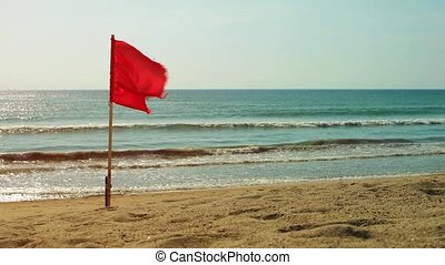 Red Safety Flag Flying on a Tropical Beach Paradise -...