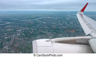 Airborne Perspective of Sprawling Urban Area over Jet Engine...