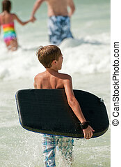 Little boy boogie boarding - Young boy going out into the...
