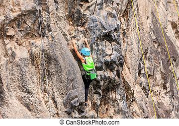 Courageous Girl Climbing A Rock Wall - Basalt Challenge Of...