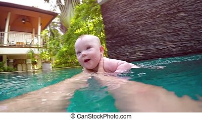 Happy Baby Boy Playing with Mommy in the Pool - Mothers arms...