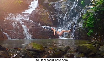 Tourist Reclining on the Rocks at Base of Natural Waterfall...