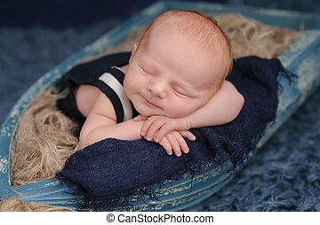 Smiling Newborn Baby Boy Sleeping in a Boat