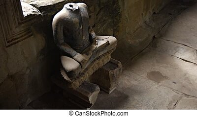 Ancient Religious Sculpture with Missing Head at Angkor Wat...