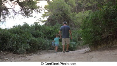 Father and son walking away in forest