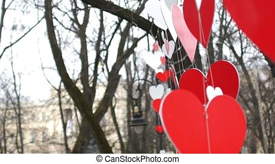 Paper red hearts decoration swaying on the wind  in the autumn park. Valentine's day concept