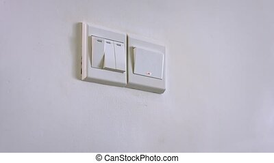 quot;Hand Using a Wall Switch to Turn off the Lights, with...