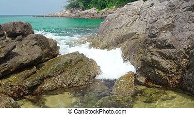 Sea Water Spills - Gentle waves wash over the rocks and into...