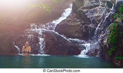 Tourist Bathing in Pool at Base of Natural Waterfall - Happy...
