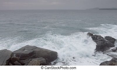 """Waves and foamy waters wash over boulders on a rocky,..."