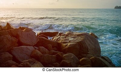 Rocks in surf zone before sunset. Thailand